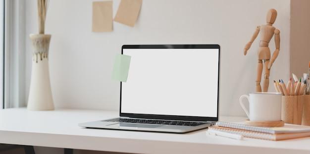 Apra il computer portatile dello schermo in bianco con la nota appiccicosa e gli articoli per ufficio