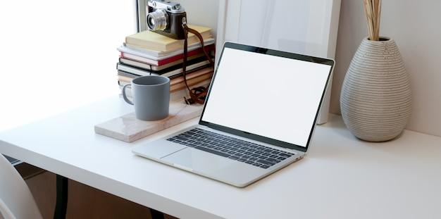Apra il computer portatile dello schermo in bianco nell'area di lavoro minima con gli articoli per ufficio