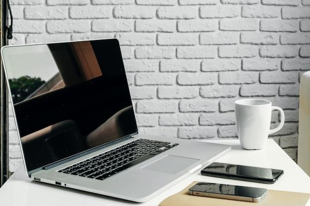 Apra il computer portatile sulla tavola vicino al sofà, l'interno domestico, concetto del posto di lavoro delle free lance