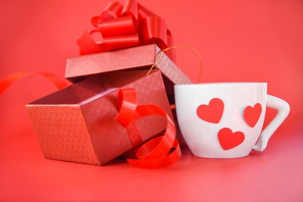 Apra il contenitore di regalo e la tazza di caffè macchiato con il giorno di biglietti di s. valentino rosso del cuore su fondo rosso