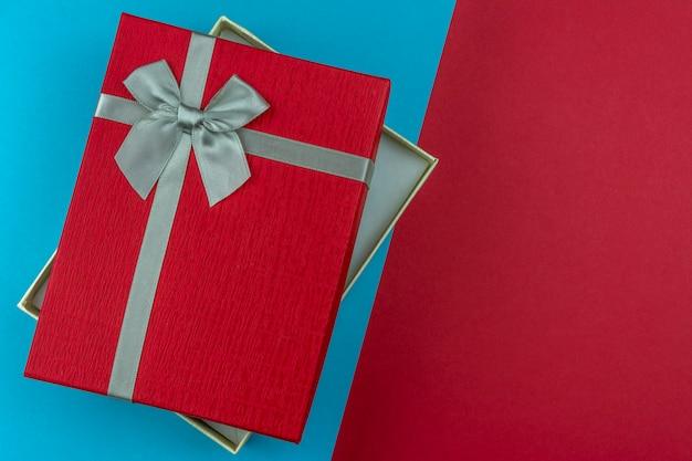 Apra il contenitore di regalo rosso con l'arco su fondo rosso e blu