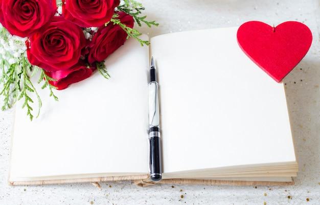 Apra il libro con le pagine in bianco e penna sopra e rose rosse e fondo del cuore del feltro