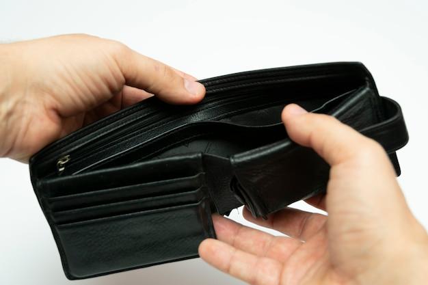 Apra il portafoglio di cuoio nero vuoto in mani su un fondo bianco, primo piano