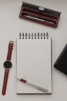 Apra il taccuino a spirale bianco con un foglio bianco e molti accessori per ufficio, un orologio da polso, un telefono cellulare, una custodia per penna e un computer portatile.