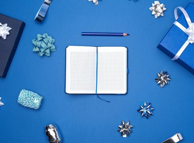 Apra il taccuino con fogli bianchi vuoti, sfondo blu con scatola