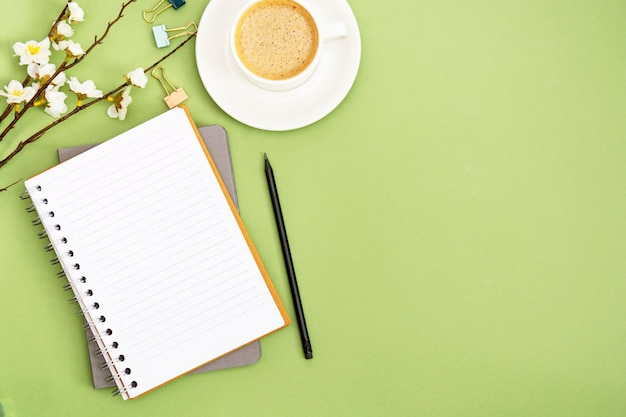 Apra il taccuino con la pagina vuota e la tazza di caffè. piano d'appoggio della primavera, spazio di lavoro su fondo verde. posa piatta creativa.