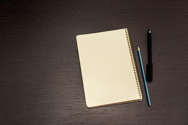 Apra il taccuino con le pagine in bianco e la penna sullo scrittorio di legno