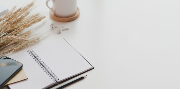 Apra il taccuino e gli articoli per ufficio sullo scrittorio bianco della tavola