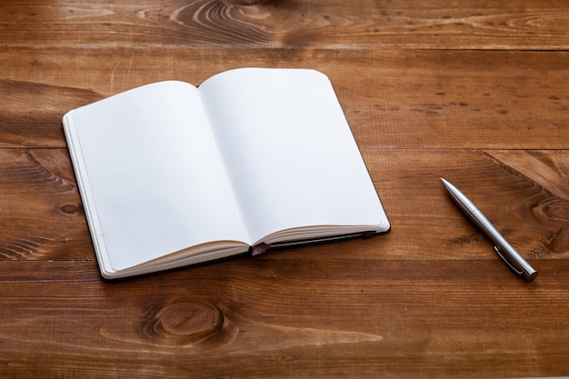 Apra il taccuino in bianco con la penna sullo scrittorio di legno marrone