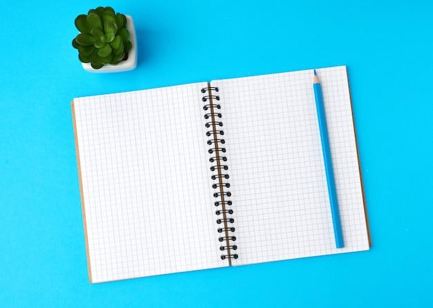 Apra il taccuino in una gabbia con il foglio bianco bianco e una matita di legno blu