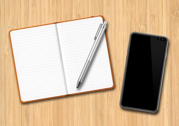 Apra il taccuino, la penna e lo smartphone su una scrivania in legno