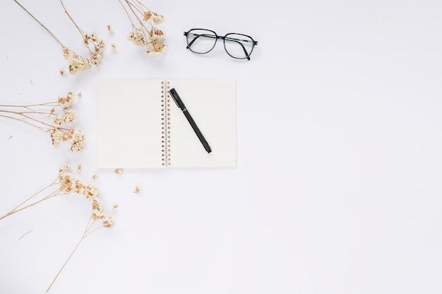 Apra il taccuino; occhiali e fiori su sfondo bianco