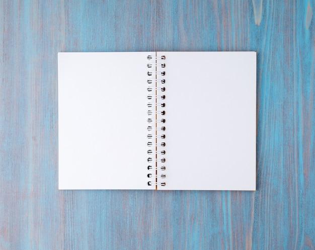 Apra il taccuino su primavera con carta bianca per appunti e disegno. sfondo chiaro, blu corteggiare
