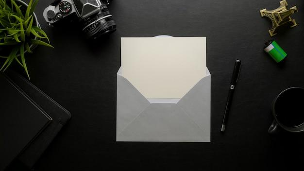 Apra la cartolina d'auguri con la busta grigia sulla scrivania scura con la macchina fotografica digitale e gli articoli per ufficio