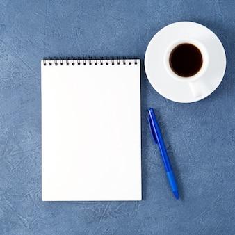 Apra la pagina bianca pulita del blocco note, la penna e la tazza di caffè sulla tavola di pietra blu scuro invecchiata, vista superiore