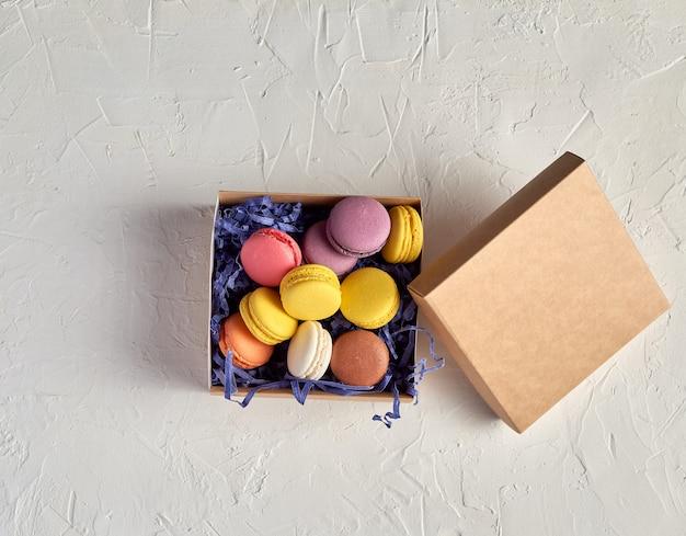 Apra la scatola di cartone con un macarons rotondo multicolore del dessert cotto al forno