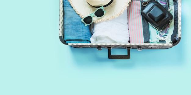 Apra la valigia con vestiti femminili per il viaggio sul blu pastello.