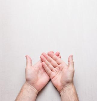 Apra le mani maschii su una vista superiore del fondo grigio, con spazio per testo.