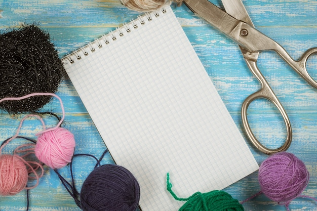 Apri il quaderno e imposta il ricamo su un tavolo di legno blu.