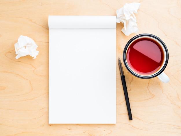 Apri il taccuino con un foglio bianco pulito per appunti e disegni, carta stropicciata, matita e tazza di tè