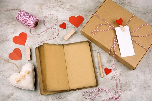 Aprire il blocco note con vecchia carta vintage, matita, confezione regalo con etichetta bianca vuota, cuori su un marmo