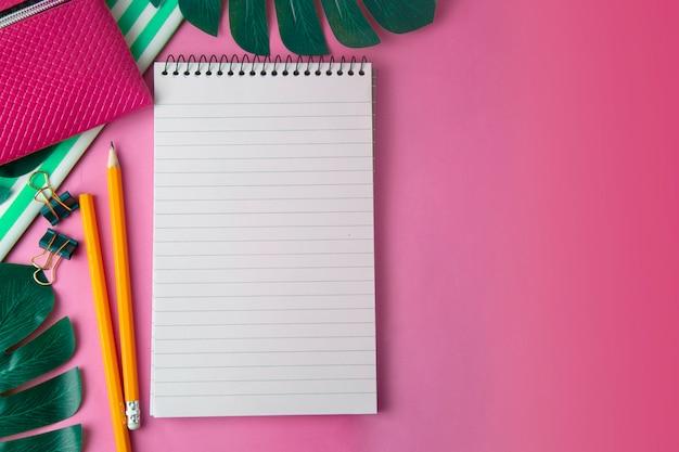 Aprire il blocco note e le foglie di monstera. modello femminile, spazio di lavoro rosa. modello.