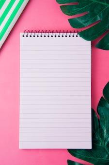 Aprire il blocco note e le foglie di monstera. modello femminile, spazio di lavoro rosa.