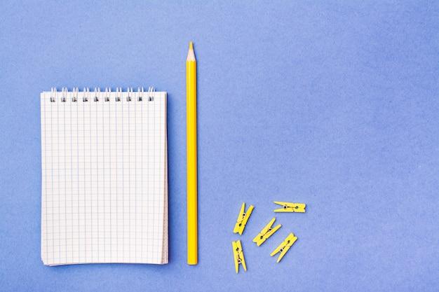 Aprire il blocco note in una gabbia a spirale, una matita gialla e morsetti su un blu
