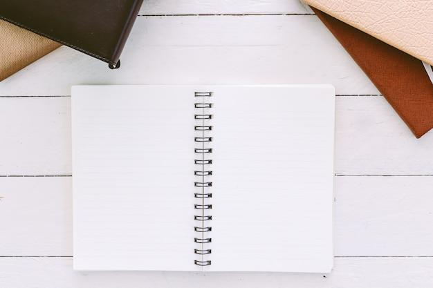 Aprire il blocco note vuoto con pagine bianche vuote sul tavolo di legno