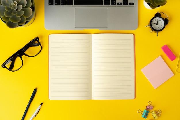Aprire il laptop con il taccuino in bianco, vista dall'alto