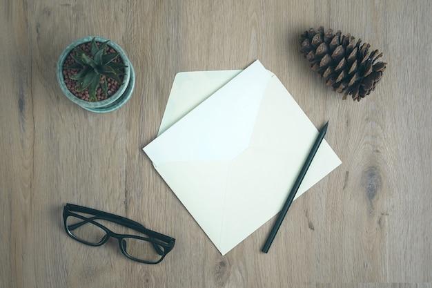 Aprire la busta verde con lettera e matita nera su una scrivania di legno rustica.