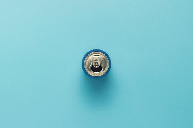 Aprire la lattina con un drink o vuoto su sfondo blu. minimalismo. concetto di giorno e notte, caffeina, bevanda energetica, vacanze. vista piana, vista dall'alto.