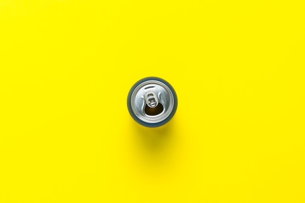 Aprire la lattina con un drink o vuoto su uno sfondo giallo. minimalismo. concetto di giorno e notte, caffeina, bevanda energetica, vacanze. vista piana, vista dall'alto.