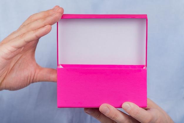 Aprire la scatola rosa nelle mani degli uomini. vista frontale. avvicinamento. copia spazio. moke up
