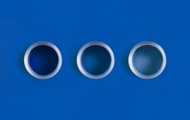 Aprire le lattine di vernice su sfondo blu classico alla moda. colore dell'anno 2020.