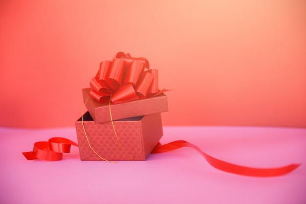 Aprire lo spazio rosso della copia del contenitore di regalo sulla scatola attuale rossa rosa con l'arco del nastro rosso per il regalo alle feste di buon natale buon anno o giorno di biglietti di s. valentino