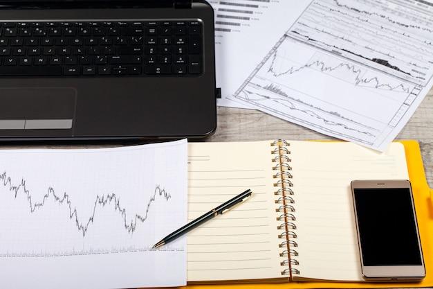 Aprire notebook, occhiali, computer, penna e smartphone su un tavolo di legno