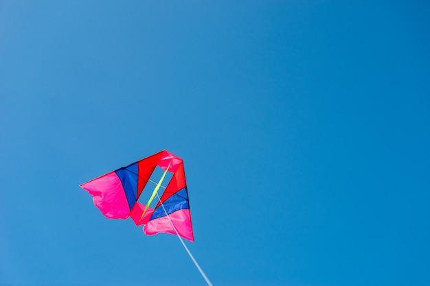 Aquilone colorato che vola contro il fondo del cielo blu