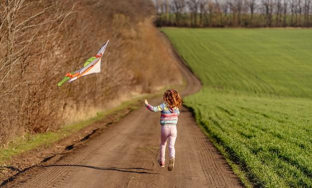 Aquilone di volo adorabile della bambina