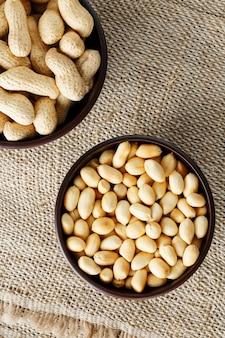 Arachidi con guscio e primo piano pelato in coppe, arachidi tostate con guscio e pelate contro un panno marrone