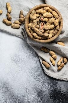 Arachidi in guscio, arachidi crude organiche, vista dall'alto, spazio per il testo