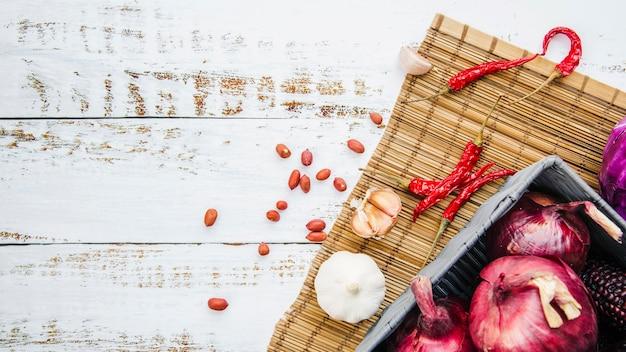 Arachidi; verdura con tovaglietta sul tavolo di legno