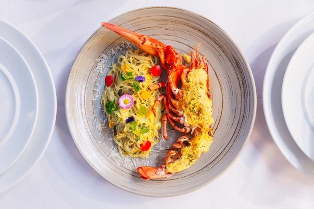 Aragosta bollita con formaggio servito con spaghetti alla carbonara decorata con fiori e petali.