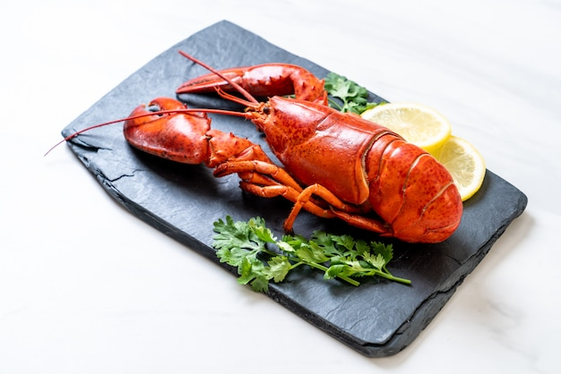 Aragosta con verdure e limone sul piatto di ardesia nera