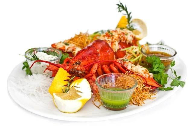 Aragosta rossa con le verdure su un piatto bianco. isolato