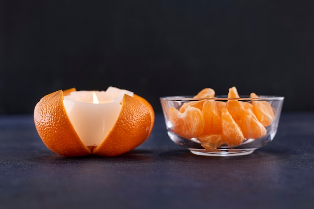 Arance a fette e candela fusa su una superficie grigia