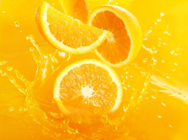 Arance fresche che cadono nel succo