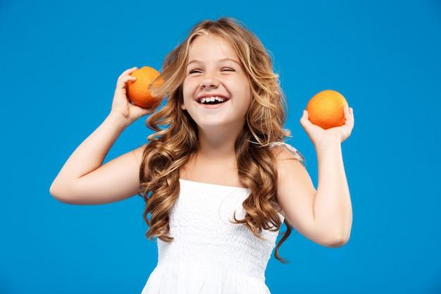 Arance giovani graziose della tenuta della ragazza, sorridenti sopra la parete blu