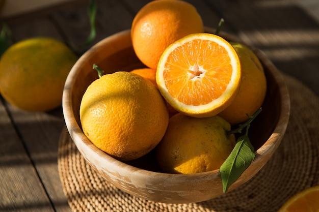 Arance in una ciotola. molti frutti delle arance fresche colti dal ramo dell'arancio. arance vista dall'alto