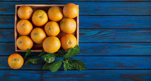 Arance mature in una cassa di legno su un fondo di legno blu.